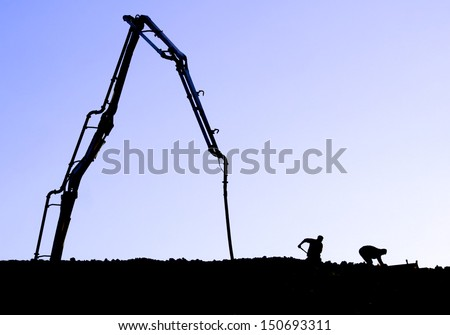 Silhouette of workers and a concrete pump  on ridge with blue mauve sky background - stock photo