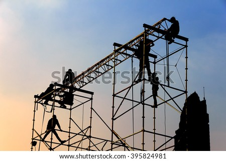 Silhouette of workmen in mounting the outdoor concert stage - stock photo