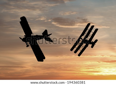 Silhouette of World War One Bi-planes and Tri-planes engaged in a dogfight. (Artist's impression) - stock photo