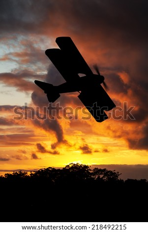 Silhouette of WWI plane at sunsent or sunrise. (artist impression) - stock photo