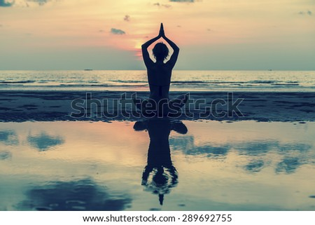 Silhouette of yoga woman sitting in lotus pose on the beach with reflection in water.