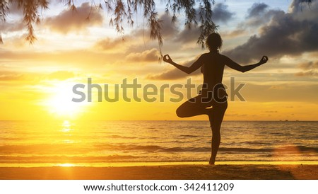 Silhouette of yoga woman standing on the beach during sunset. - stock photo