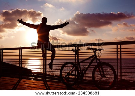 silhouette of young and active sportsman and his mountain bike sitting on the railing with outstretched arms near the ocean and looking far away at the sunset  - stock photo