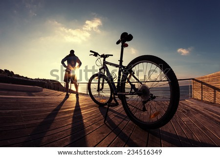 silhouette of young and active sportsman and his mountain bike standing near the ocean and looking far away at the sunset - stock photo