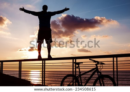 silhouette of young and active sportsman and his mountain bike standing on the railing with outstretched arms near the ocean and looking far away at the sunset  - stock photo