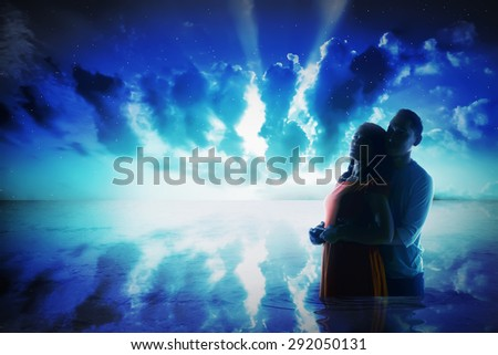 Silhouette of young asian couple on the sea at night time - stock photo