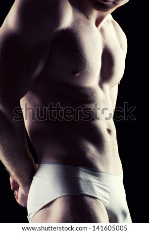 Silhouette of young athlete bodybuilder man on black - stock photo