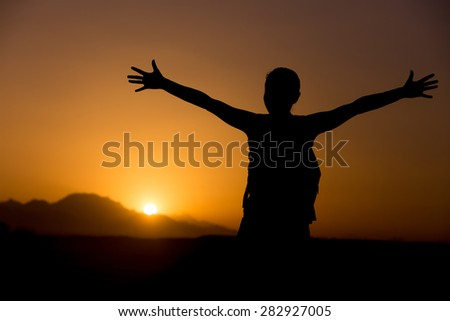 Silhouette of young backpacker person standing with raised arms feeling happy in colorful picturesque landscape, sun rising or setting in mountains on horizon