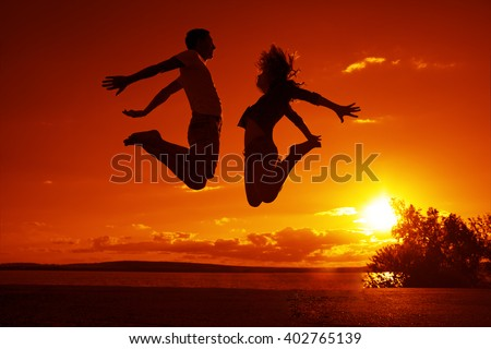 Silhouette of young barefoot Couple jumps on sunset beach over the water texture, orange or yellow sky and rising sun with rays - stock photo