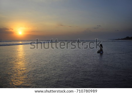 Silhouette of young beautiful asian woman sitting on sand water free and relaxed looking at the sun on sunset beach in Bali Indonesia with dramatic orange sky in yoga wellness and meditation