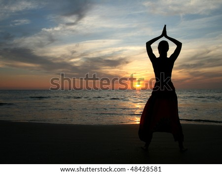 silhouette of young beautiful woman on the beach - stock photo