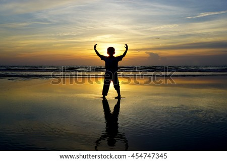 Silhouette of young boy Raising His Hands or Open arms when sun rising up - stock photo