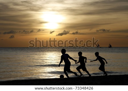 Silhouette of young boys playing at the beach during sunset - stock photo