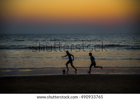Silhouette of young boys playing football at the beach during sunset