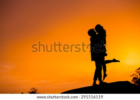 silhouette of young couple enjoying moments during sunset