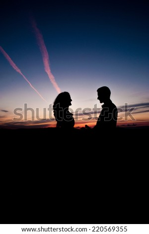 Silhouette of Young couple in love bride and groom posing in a field on beautiful sky sunset background, in their wedding day in the summer,holding hands. Series. - stock photo