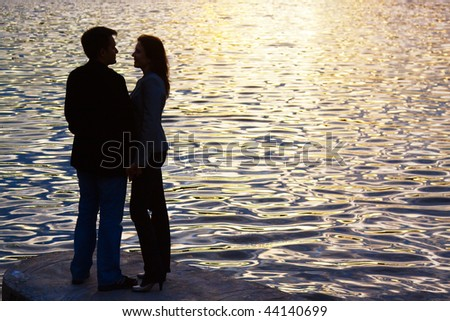 Silhouette of young couple near water