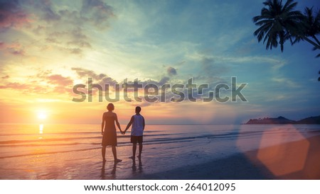 Silhouette of young couple on their honeymoon standing on Sea beach at amazing sunset. - stock photo