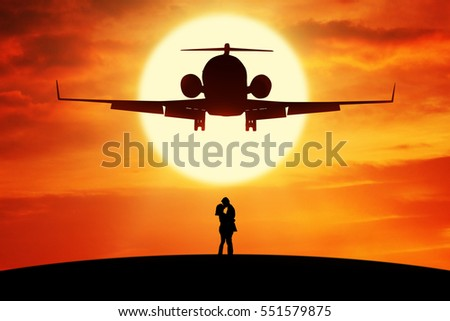 Silhouette of young couple standing on the hill and kissing under a flying airplane at sunset time