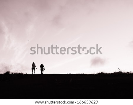 Silhouette of young couple walking side by side. - stock photo