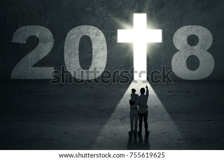 Silhouette of young family pointing at a bright crucifix shaped a door with numbers 2018