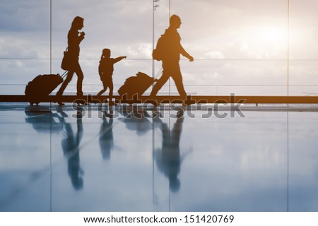 Silhouette of young family with luggage walking at airport, girl showing something through the window
