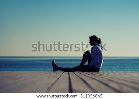 Silhouette of young female athlete resting after an intensive exercises in beautiful evening at sunset, sportswoman sitting on the wooden pier against ocean while resting after an active run outdoors