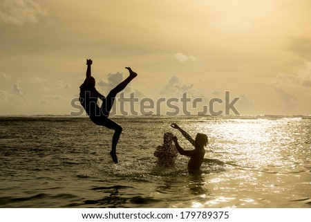 Silhouette of young girl jumping out of the ocean, which throws strong two man on the background of the expiring sunset. Single shooting - stock photo