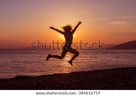 Silhouette of young girl jumping with hands up on the beach at the sunset