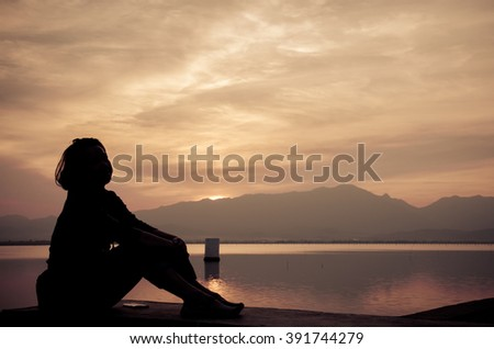 Silhouette of young girl sitting at the sunset against the sun