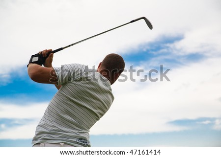 Silhouette of young golfer in swing pose. - stock photo