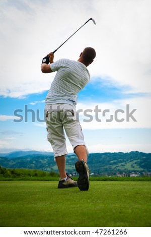 Silhouette of young golfer in swing pose.