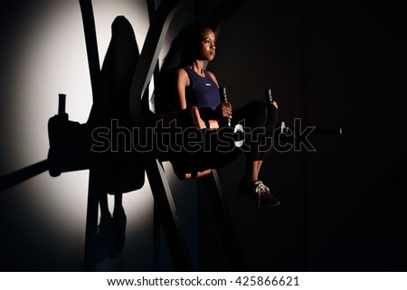 Silhouette of young gorgeous african-american woman fitness instructor working out at the gym