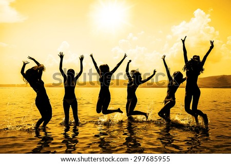 Silhouette of young group of people jumping in ocean at sunset Team of adult girl stand in water on summer beach against blue sky with clouds Water splash Hair fly in air Empty space for inscription - stock photo