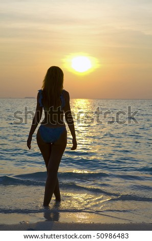 Silhouette of young harmonious woman of going in ocean towards sunset..