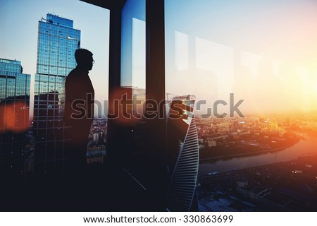 Silhouette of young intelligent man managing director resting after late business meeting while standing near big office window background with copy space for your text message or promotional content - stock photo