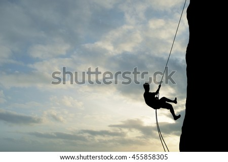 Silhouette of young man abseiling down from a cliff, sun, beautiful colorful sky and clouds behind. Climber rappelling from a rock.