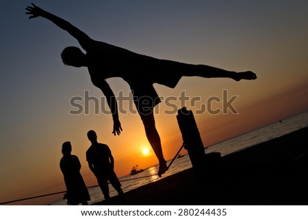 Silhouette of young man balancing jumping on slackline during sunset at a beach in Manabi - stock photo
