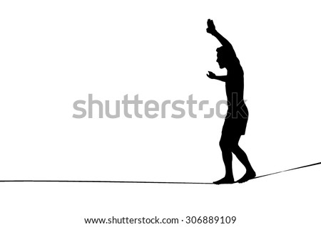 Silhouette of young man balancing on slackline. Slackliner balancing on tightrope silhouette.