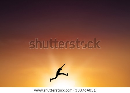 Silhouette of young man enjoy vacation and jumping on the air at sunset time - stock photo