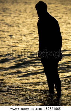 Silhouette of young man in sunset. - stock photo