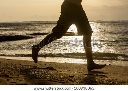 Silhouette of young man jogging along the ocean shore at sunset