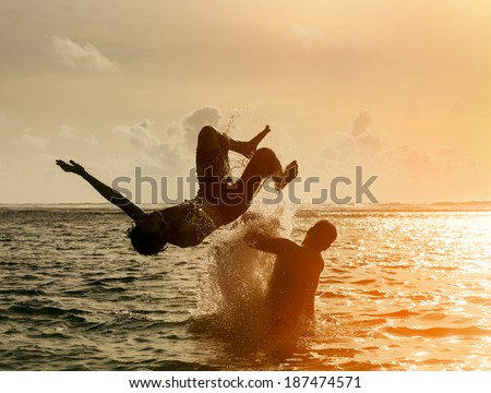 Silhouette of young man jumping out of the ocean, which throws strong two man on the background of the expiring sunset - stock photo