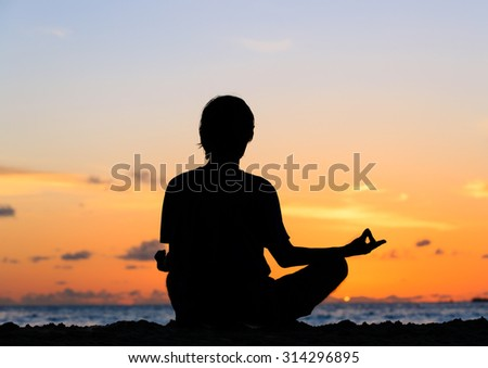 Silhouette of young man meditating at sunset beach