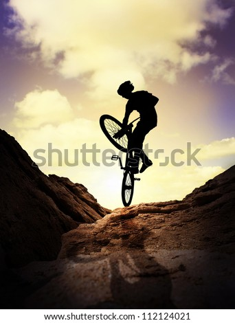 Silhouette  of young man on the mountain bike over purple sunset sky - stock photo