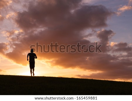 Silhouette of young man running during sunset - stock photo