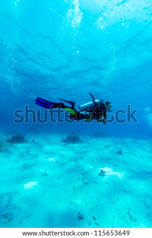 Silhouette of Young Man Scuba Diver between Water Surface and Sea Bottom - stock photo
