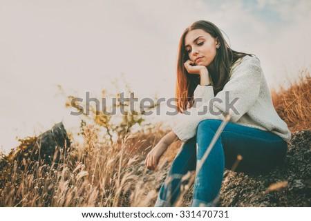 Silhouette of young man sitting on sunset or sunrise. Confident teenage boy thinking on cliff stone. Hope. Sadness. Freedom. - stock photo