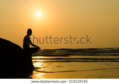 silhouette of young man sitting on the edge of rock at sunrise