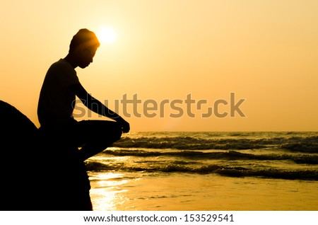 silhouette of young man sitting on the edge of rock at sunrise - stock photo